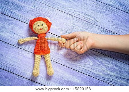 Crocheted Doll Girl And This Girl's Hand On The Wooden Background With Free Place For Your Inscripti