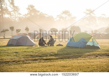 two men sitting near camping tent in beautiful morning at campsite of Phu Kradueng National Park Loei Thailand