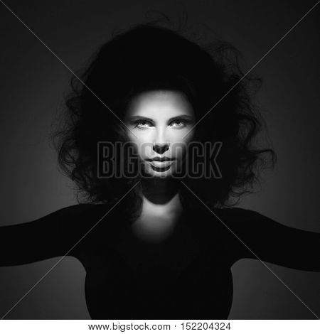 Black and white studio fashion portrait of beautiful woman with volume wavy hair. Big hair