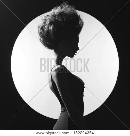 Black and white studio photo of elegant woman on geometric background