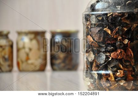Detail of a glass jar with dried mushrooms closeup. Canned pickled mushroom in the background.