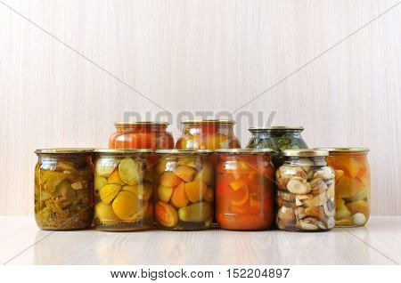 Many inverted glass jars with canned pickled vegetables on wooden surface: peppers tomatoes cucumbers mushrooms.