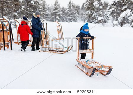 Beautiful family of father and kids enjoying snowy winter day outdoors having fun sledging