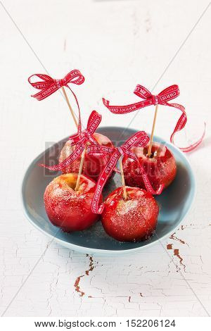 Homemade candied apples with a red bow on a wooden background