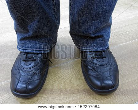 Man stands in jeans and in casual shoes. Man in jeans and everyday shoes. Man in jeans and casual shoes. Male legs in jeans and boots.