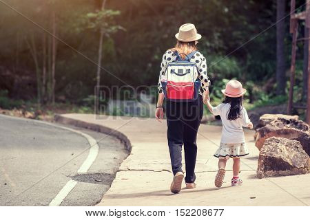 Mother and daughter walking holding hands at park. They are wearing warm clothes, autumn season. Lot of free space on left to add writings. Family lifestyle concept