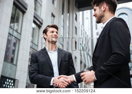 Two cheerful young businessmen shaking hands in the city