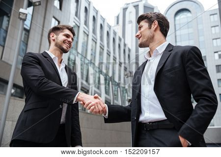 Two happy successful young businessmen standing and shaking hands near business center
