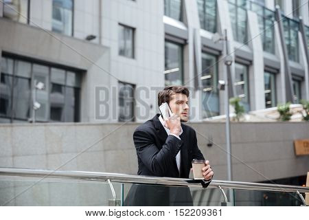 Handsome businessman talking on mobile phone and drinking coffee in the city