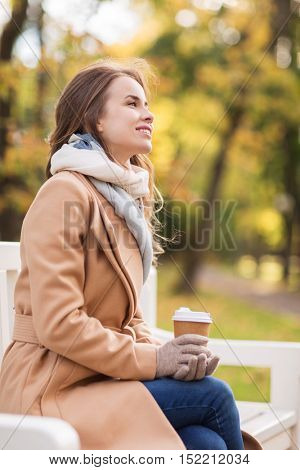 season, hot drinks and people concept - beautiful happy young woman drinking coffee or tea from disposable paper cup sitting on bench in autumn park