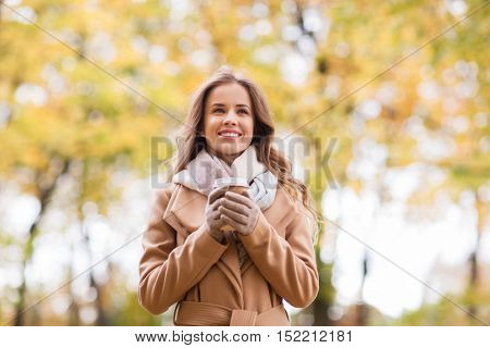season, hot drinks and people concept - beautiful happy young woman drinking coffee or tea from disposable paper cup in autumn park