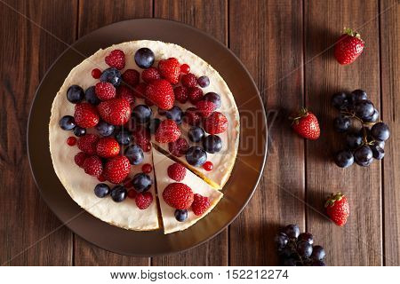 Close up. Delicious Homemade creamy New York Cheesecake with berries on dark wooden table. Top viev. Cream mousse cake.
