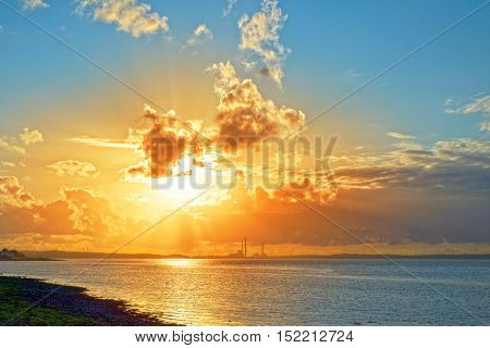 beautiful orange sunset over a power station on the river shannon in ireland