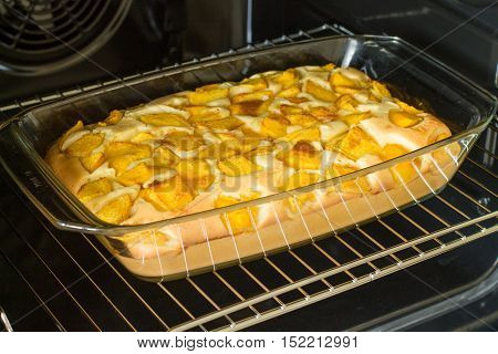 Sweet pie with peach in glass brazier inside oven.