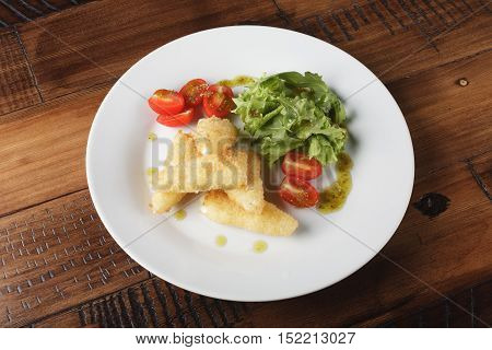 Breaded cheese (deep-fry) with tomatoes and greens in a white plate. Wooden background