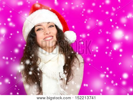 girl in santa hat portrait on pink color background, christmas holiday concept, happy and emotions