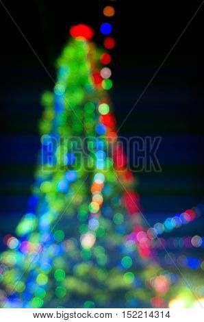 An abstract blurred background with a bokeh in a shape of christmas tree with star.