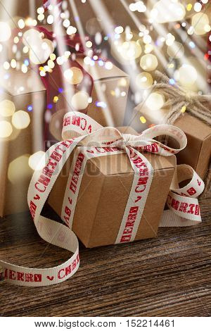 Handmade gift boxes on wooden background close up with glimming bokeh and light