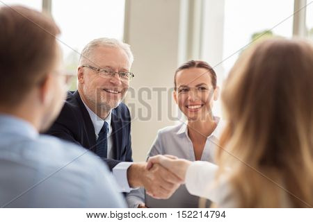business, people, gesture, cooperation and partnership concept - smiling senior businessman making handshake with woman at office