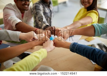 education, school, teamwork and people concept - close up of international students hands making fist bump gesture