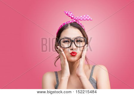 Fashion portrait of asian girl with sunglass standing on pink sending a kiss.