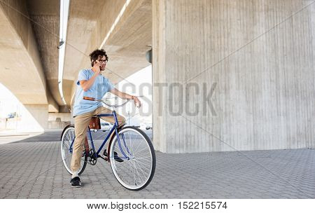 people, communication, technology, leisure and lifestyle - hipster man texting on smartphone with fixed gear bicycle on city street
