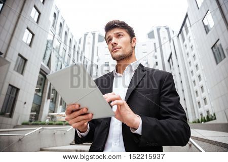 Handsome young businessman standing and using tablet near business center