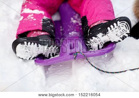 childhood, footwear, fashion, season and people concept - close up of kids feet in winter boots on sled