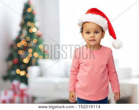 holidays, children and people concept - beautiful little african american baby girl in santa hat over living room with christmas thee lights background