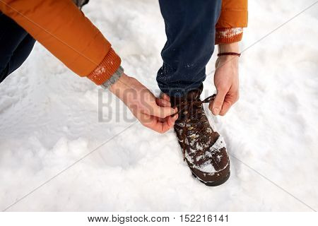 people, footwear and season concept - close up of man tying boot shoelaces outdoors in winter
