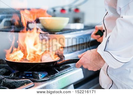 Chef doing flambe to dish in pan with large fire flame