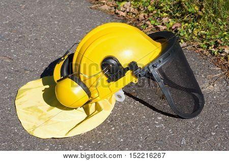 yellow construction helmet on a gray pavement