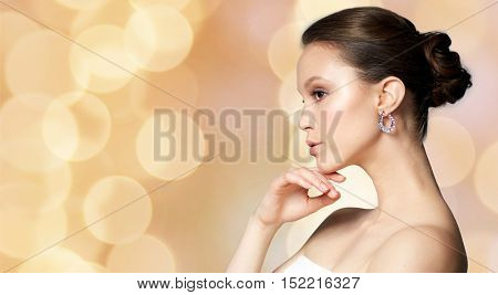 beauty, jewelry, accessories, people and luxury concept - beautiful asian woman with earring over holidays lights background