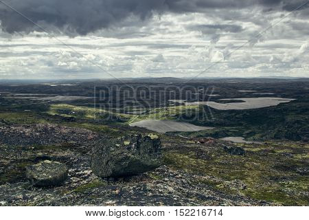 Highlands valley with views of the lake and the green hills in a sunny cloudy day. Arctic summer the tundra Norway.
