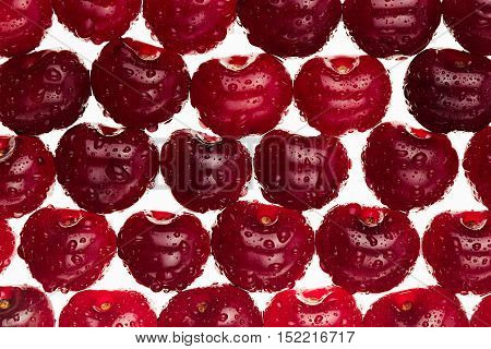 Cherry background. Ripe fresh glossy rich cherries on white background. Macro. Texture. Pattern. Fruit background. Food background.