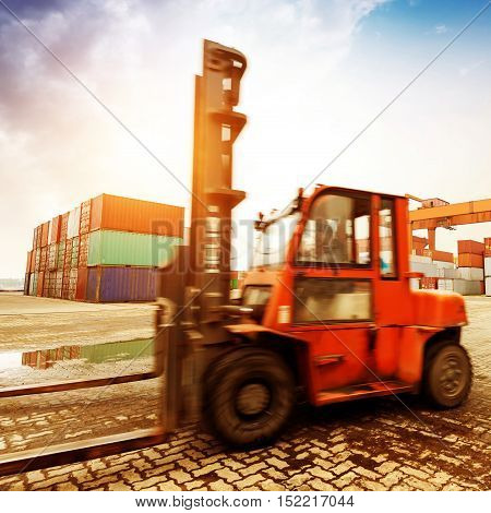 When the container terminal at dusk work cranes and forklift.