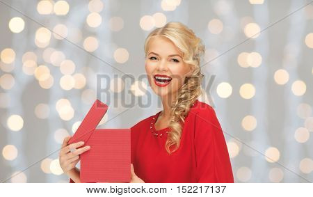 christmas, holidays, valentines day, birthday and people concept - laughing woman in red dress with gift box over lights background