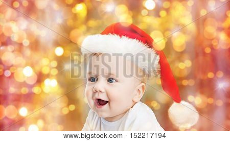 childhood, christmas, holidays and people concept - beautiful little baby boy in christmas santa hat over blue lights background
