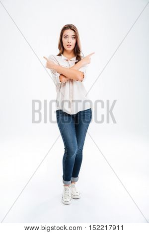 Attractive young woman standing and pointing left and right over white background