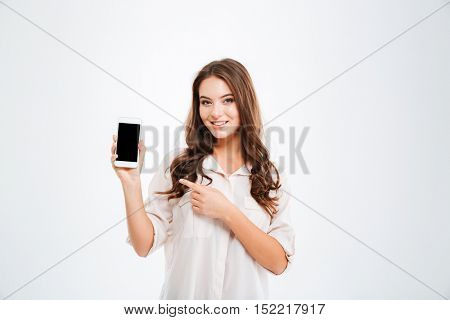 Happy beautiful young woman with long curly hair holding blank screen mobile phone and pointing finger over white background