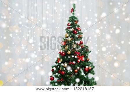 holidays, celebration and home concept - christmas tree in living room over window curtain
