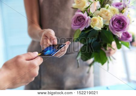 Customer giving credit card to florist at flower shop, closeup