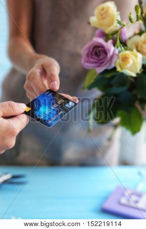 Customer giving credit card to florist at flower shop, closeup