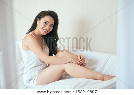 Attractive smiling Vietnamese woman sitting in her comfy bed