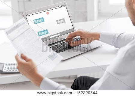 business, technology, internet, online communication and people concept - close up of businessman with messenger on laptop computer screen working at office