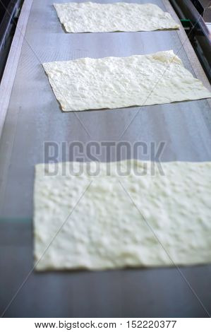 Pita on the production line at the bakery .