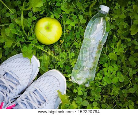 Sneakers bottle of water and apple on fresh green grass. Sports in the open air. Top view