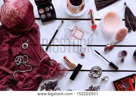 Female bodystocking, perfume with different cosmetic and different accessories on a white background