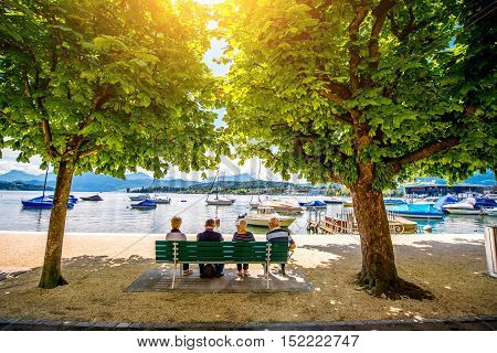 Lucerne, Switzerland - June 27, 2016: View on the park with elder people sit on the bench near Lucerne lake in Lucerne city in Switzerland. Swiss pension system is one of the best in Europe