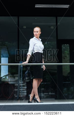 Full length portrait of a serious businesswoman standing outdoors and leaning on the glass railing